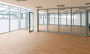 Large office with wooden flooring and a glass partitioning wall